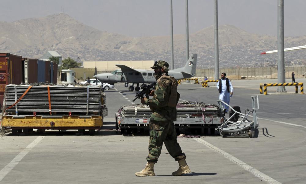 A Taliban soldier walks on the tarmac at Hamid Karzai international airport in Kabul, Afghanistan.