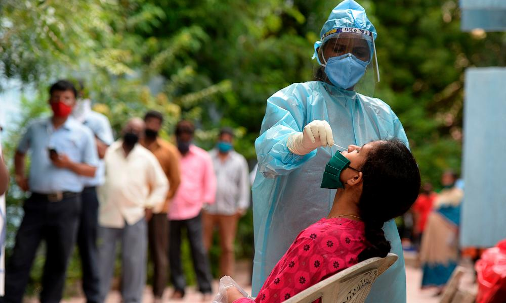 A health worker wearing a PPE suit tests a woman for Covid-19 in Hyderabad on Friday