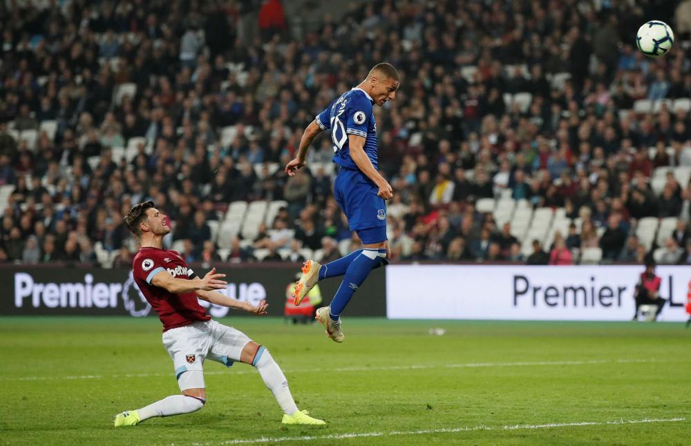 Everton's Richarlison thumps a header against the crossbar.
