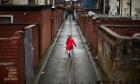 A young girl spends the half term school holiday playing in an an alleyway.