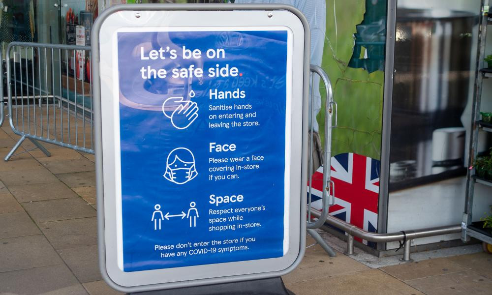Signage outside a Tesco store asking people to wear masks, maintain distance and wash hands