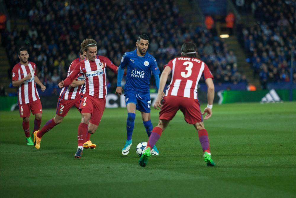 Riyad Mahrez takes on Filipe Luis before being fouled by Antoine Griezmann.