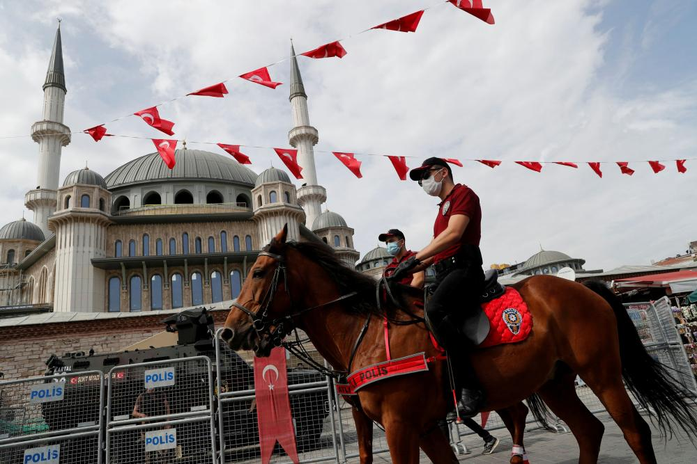 Members of Istanbul Police Department Mounted Unit patrol against people not wearing protective face masks at Taksim Square.