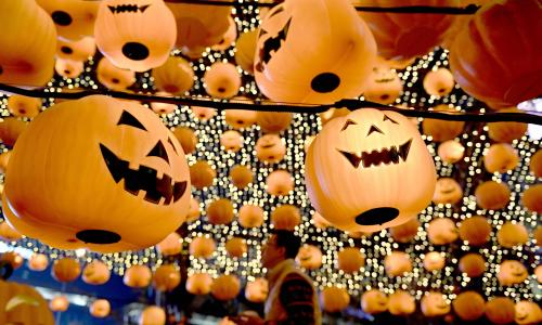 A man walks past a pumpkin lantern display in a shopping centre to mark Halloween