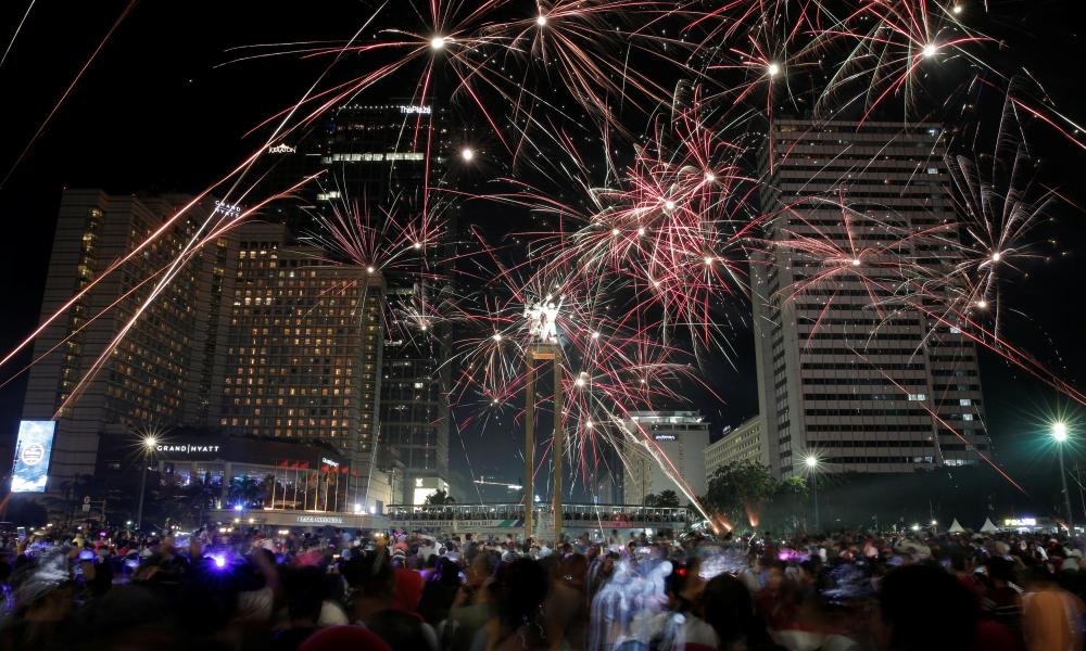People watch fireworks explode around the Selamat Datang monument during New Year's Eve celebrations in Jakarta, Indonesia