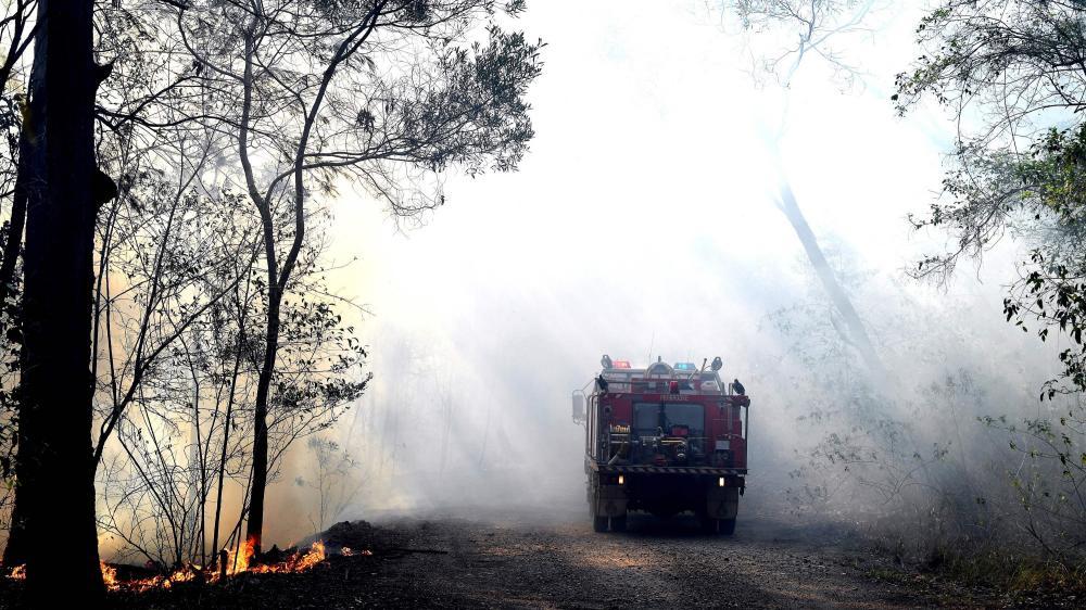 A fire truck drives through bushfire smoke.