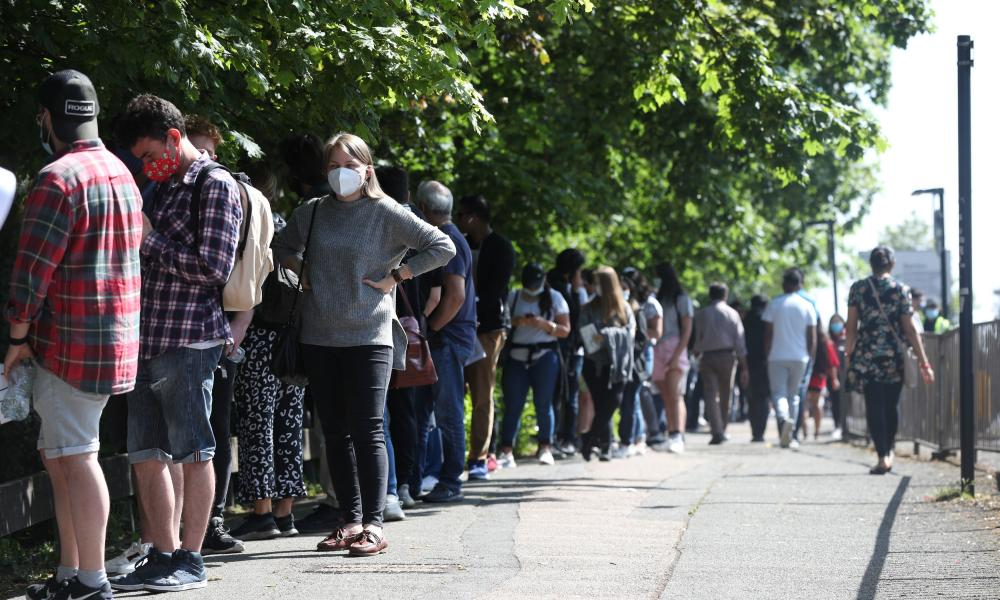 A queue of people waiting for vaccine outside Belmont health centre in Harrow, London