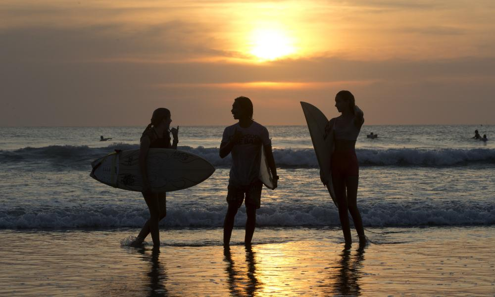 Surfers carry their boards as they watch a sunset at Kuta beach, Bali, Indonesia.