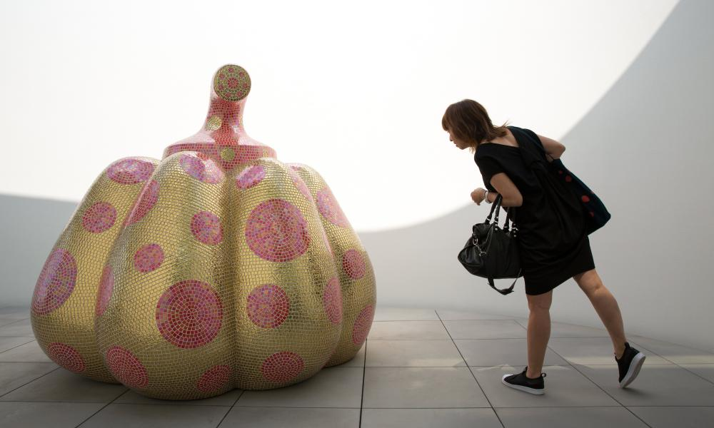 A visitor looks at the sculpture titled Starry Pumpkin during a media preview of the museum