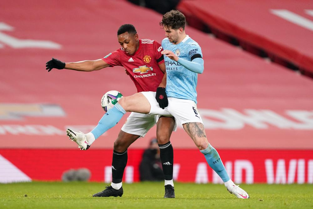 John Stones puts in a tackle on Anthony Martial