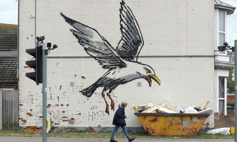 A gull eats 'chips' of insulation material from a skip in one of Banksy's four Spraycation works in Lowestoft, Suffolk.