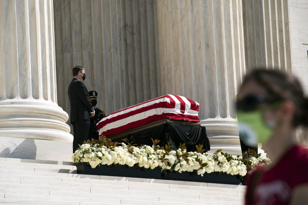 Mourners walk by Ginsburg's flag-draped casket.