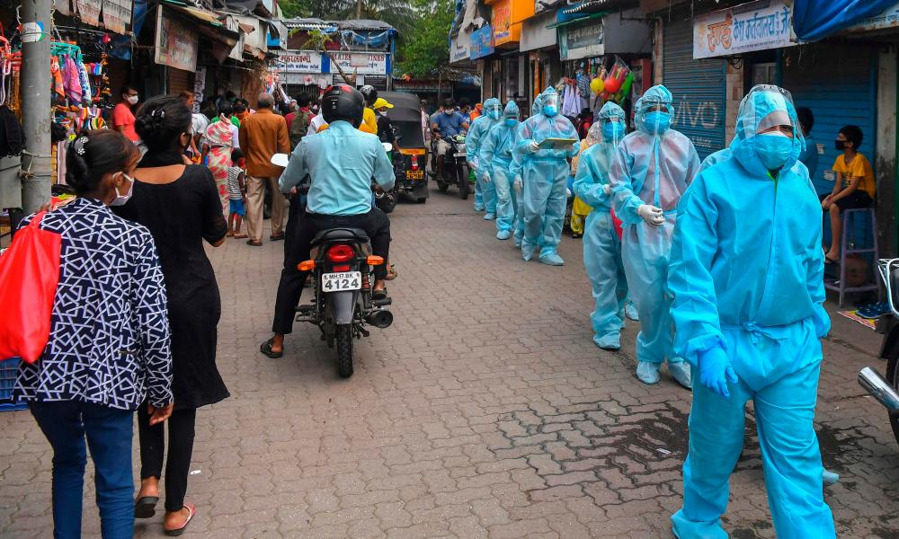Medical staff walk through a market for a door-to-door medical screening inside a market in Mumbai on 17 June 2020