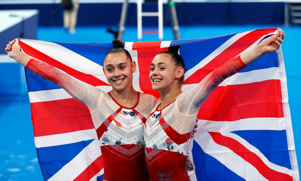 Jennifer and Jessica Gadirova in the gymnastics arena holding up a union jack behind their backs between them