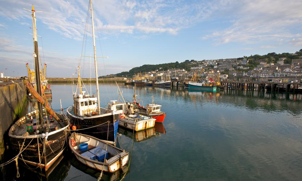 Fishing boats in the harbour on a sunny blue-sky day in Newlyn, Cornwall, UK