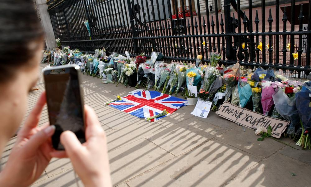 A woman takes pictures of flowers in tribute to Prince Philip outside Buckingham Palace in London