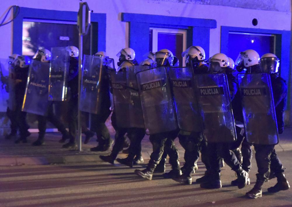 Police officers block the street during a protest in Niksic, Montenegro, on Wednesday night.