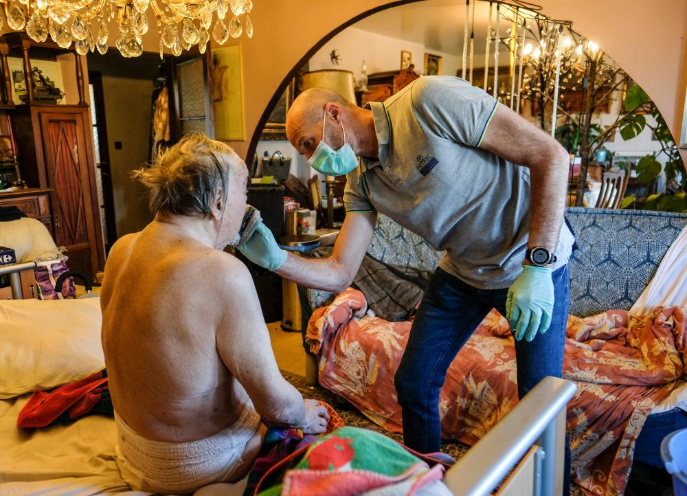 A nurse cares for a resident at a care home in Ciney, Belgium, in this picture taken earlier in April