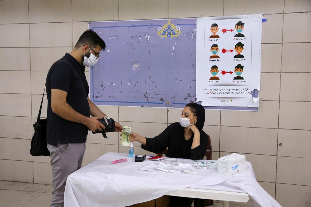An man buys hand sanitiser from a woman at a metro station in Tehran.
