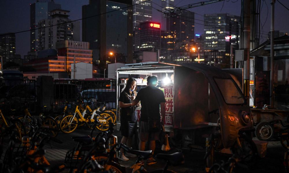 People buy food from a street vendor near a subway exit in Beijing on 10 June 2020.