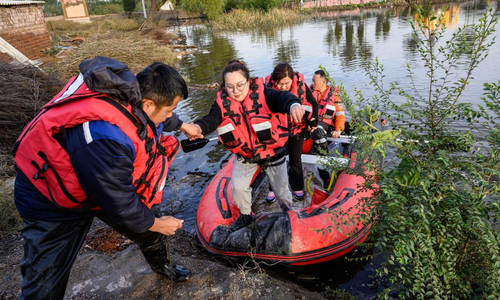 Rescuers evacuating residents in a flooded area after heavy rain in Jiexiu, Shanxi province, China