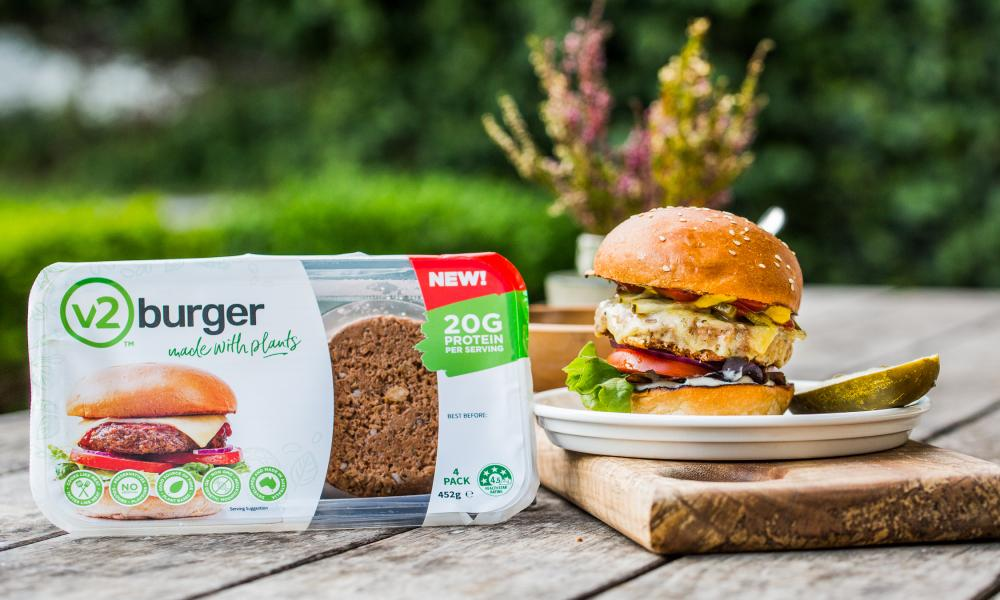 A packet of v2foods burgers and a cooked burger on a plate