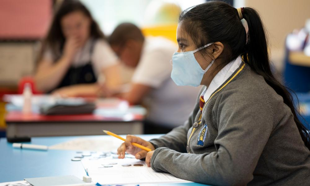A pupil wears a face mask in a classroom.