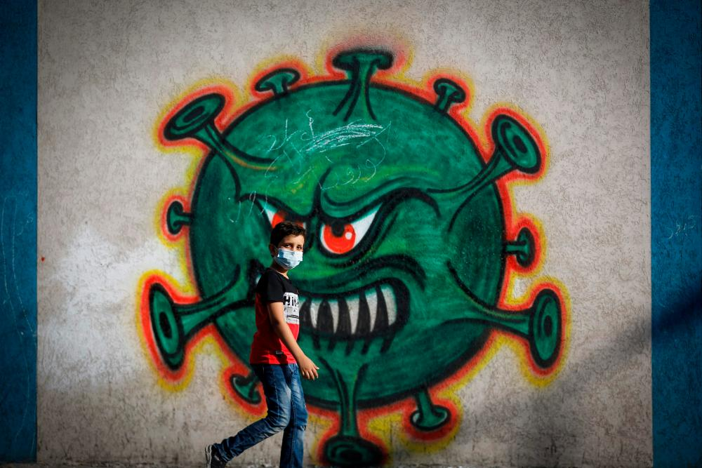 A boy walks past coronavirus-themed street art in Gaza city.
