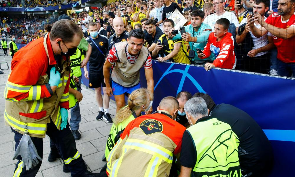 Cristiano Ronaldo checks on a steward after she was hit by a ball.