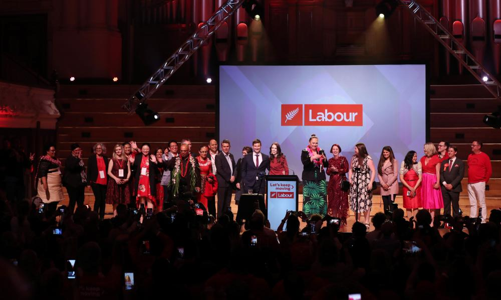 Jacinda Ardern, her partner Clarke Gayford and party members gather on the stage at the Labour Party's event