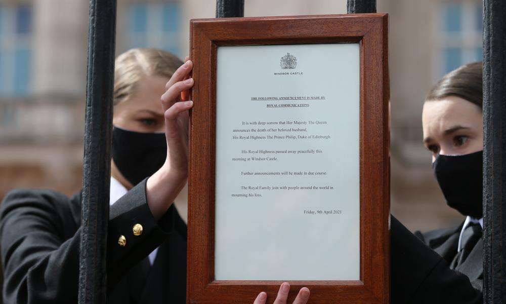 Members of the royal family staff put the official announcement of the Duke of Edinburgh's death on the fences outside Buckingham Palace