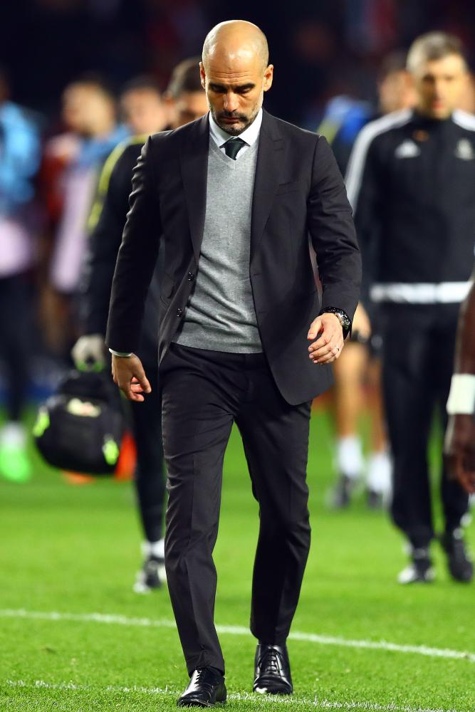 Manchester City manager Pep Guardiola looks deep in thought as he heads back to the dressing room at half-time.
