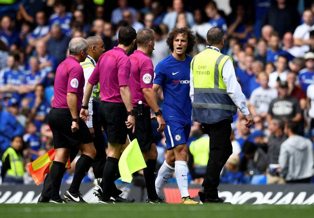 David Luiz remonstrates with referee Craig Pawson as he walks off at half-time.