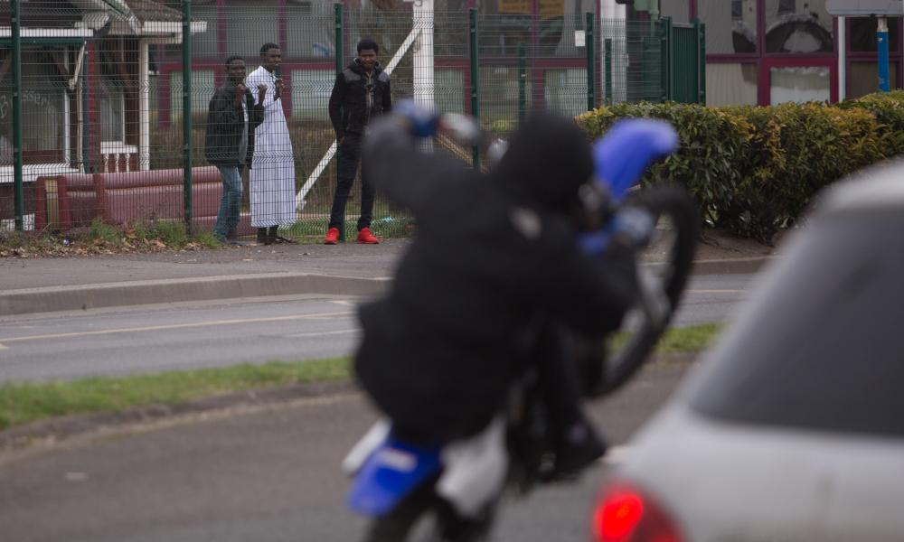 Teenagers in the Parisian suburb of Argenteuil watch a dirt bike rider pull a wheelie