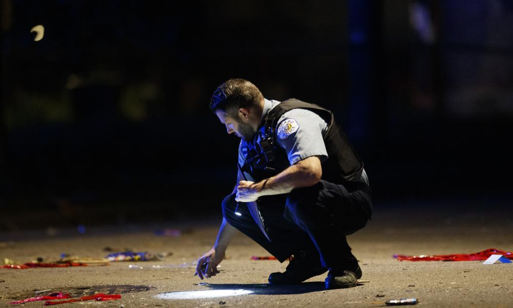 A police officer at the scene of a shooting on Sunday in Chicago , where at least a dozen people were killed in a weekend of violence.