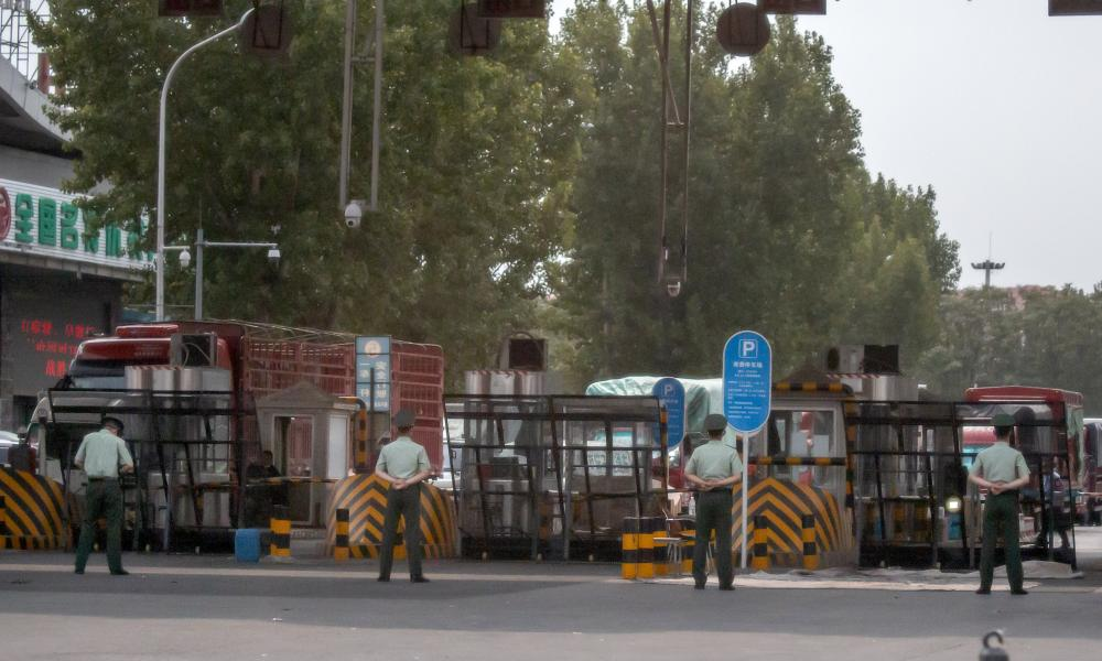 Chinese paramilitary police stand guard at barricaded entrances to the Xinfadi wholesale food market district in Beijing on Saturday.