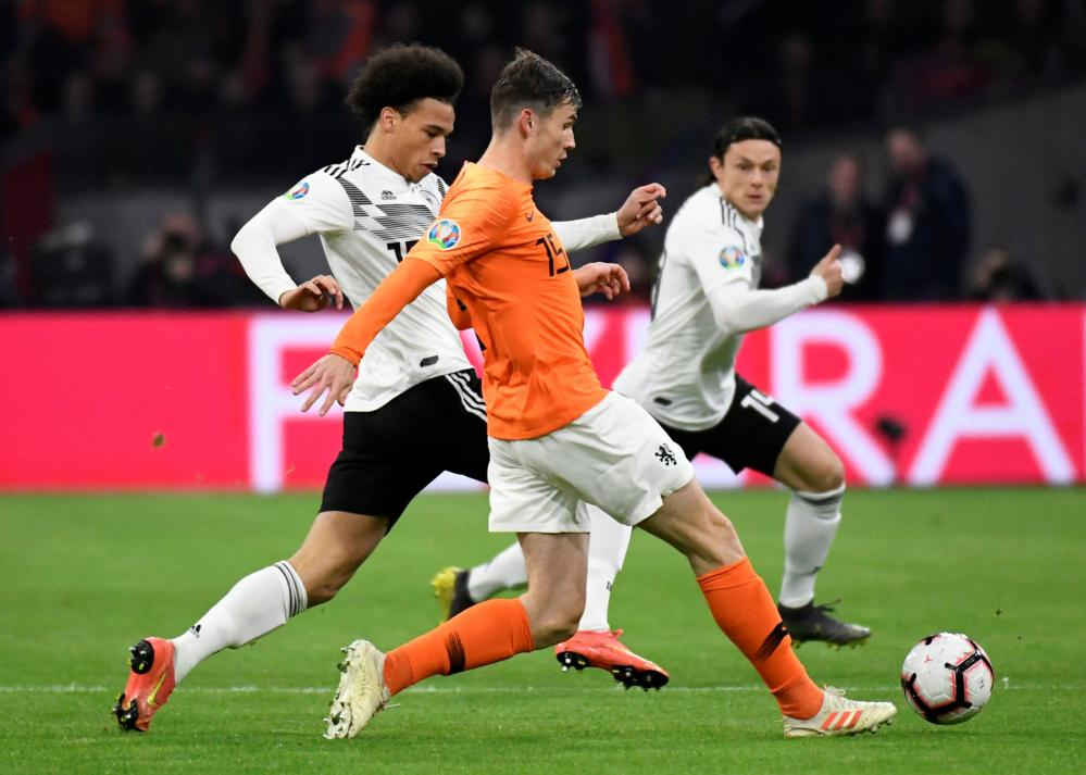 Netherland's Marten de Roon in action with Germany's Leroy Sane.