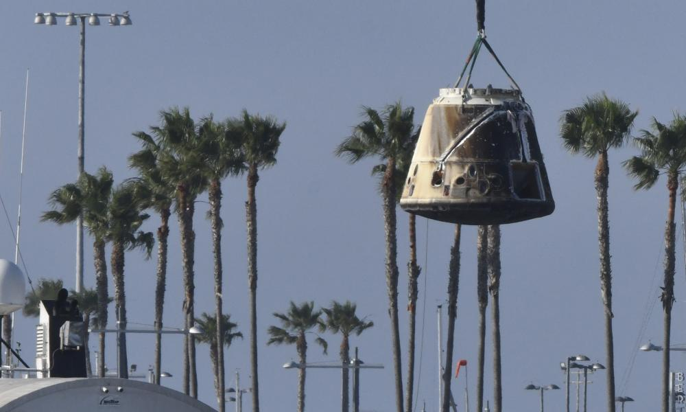 A spaceship capsule being lifted by a crane
