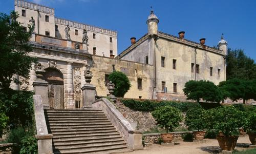 The front facade of Catajo Castle with a stone staircase leading up to a large entrance gate. Italy.