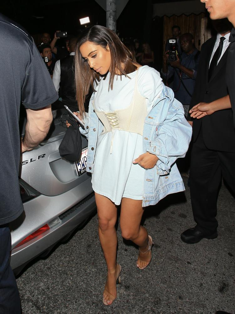 Kim Kardashian wearing a corset and chambray T-shirt in August.