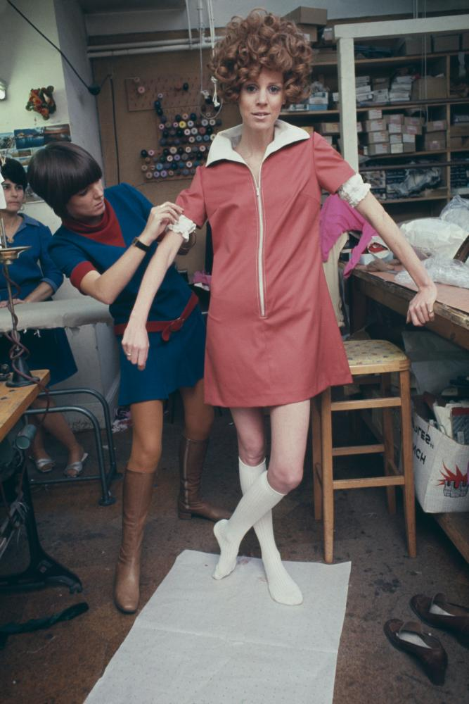 Mary Quant fits a zip-up mini dress on a model in her design studio in Londo, 1967
