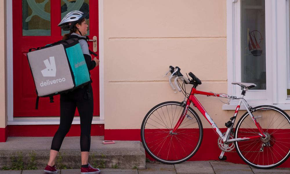 A young woman working in the 'gig economy', for Deliveroo, the takeaway food delivery company.