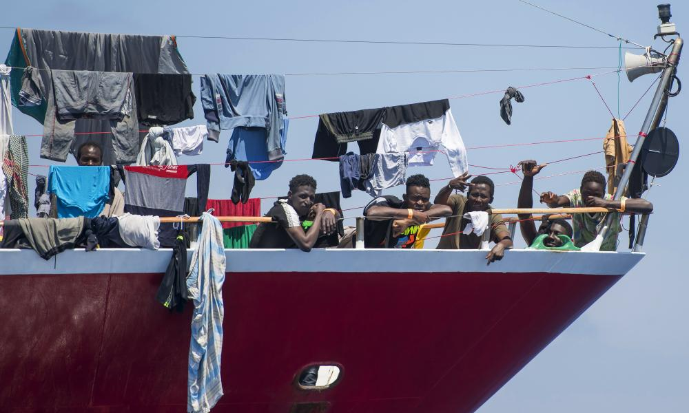 Migrants dry their clothes omboard a tourist boat 20km from Malta, on Tuesday 2 June