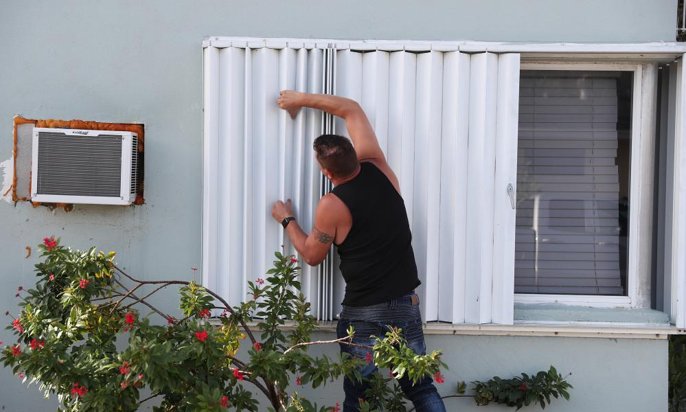 Anthony Perrone pulls the hurricane shutters closed on his home as Hurricane Isaias approaches Florida