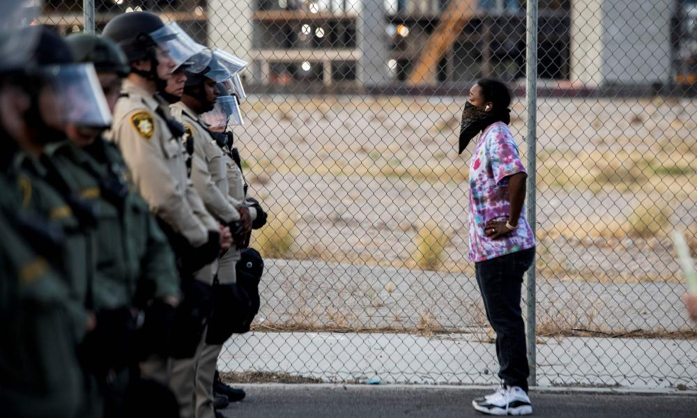 """A female protester stands in front of police officers yesterday in downtown Las Vegas, as part of a """"Black lives matter"""" rally in response to the death of George Floyd."""