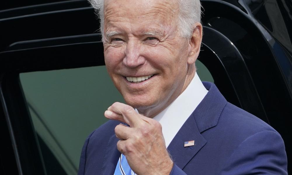 President Joe Biden crosses his fingers as he responds to a question about the short term debt deal as he arrives Air Force One at O'Hare International Airport in Chicago. While in the Chicago area, Biden will highlight his order to require large employers to mandate COVID-19 vaccines for its workers during a visit to a construction site.
