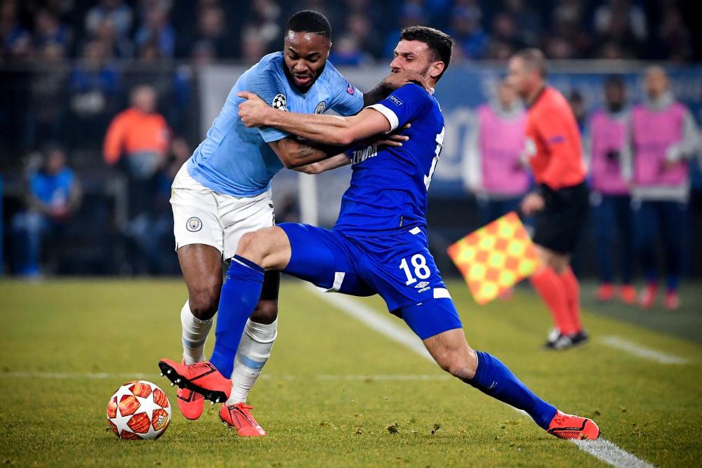 Schalke's Daniel Caligiuri (right) tussles with Manchester City's Raheem Sterling.