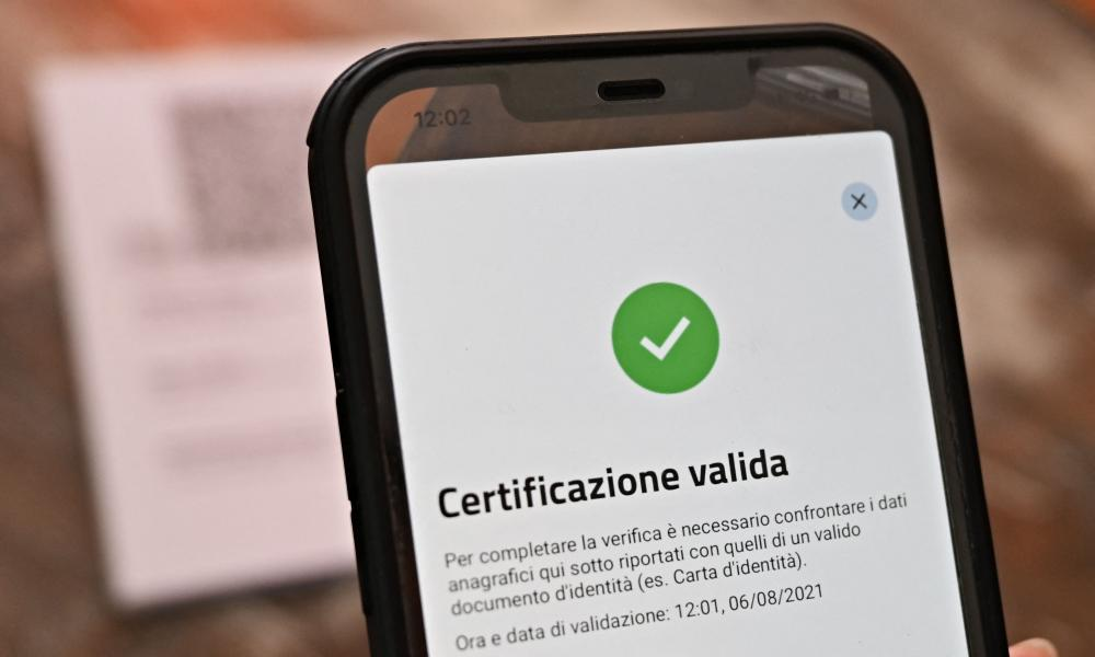 A bar owner shows a valid Green Pass on the VerifyC19 mobile phone application in central Rome.