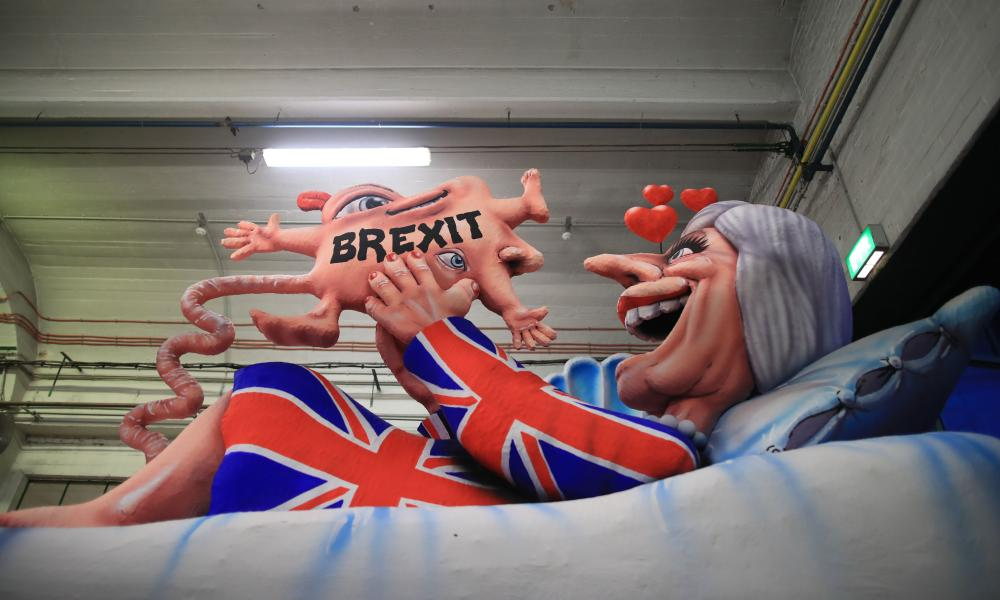 A carnival float depicting Theresa May giving birth to Brexit