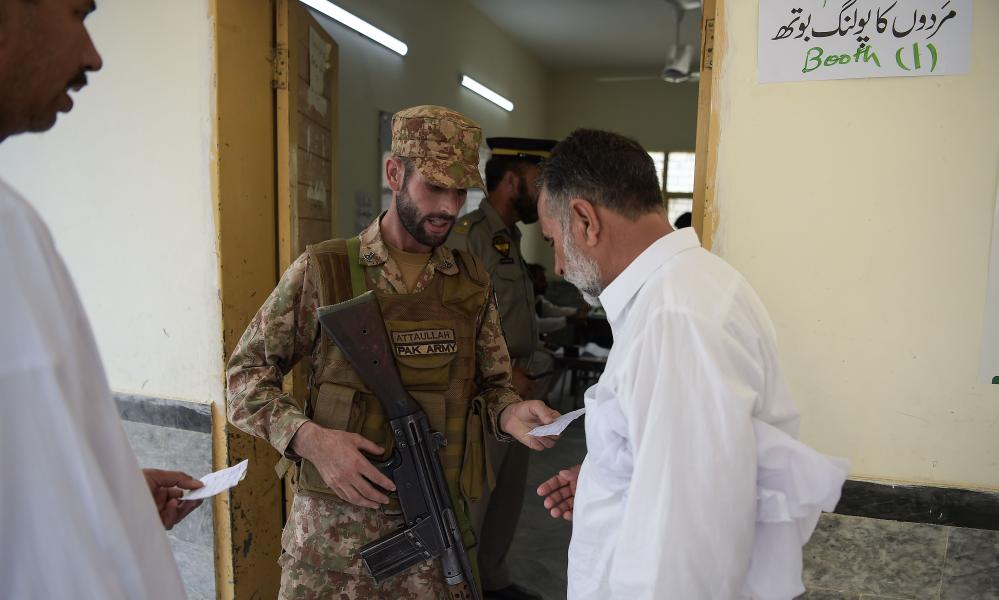 A Pakistani soldier checks a voter's information at a polling station in Islamabad.